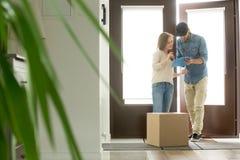 Jeune femme recevant la boîte en carton de colis du messager à la maison photos stock