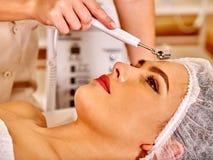 Jeune femme recevant le massage facial électrique Photo stock
