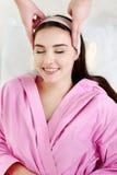 Jeune femme recevant le massage facial avec les yeux fermés dans une station thermale s Images libres de droits