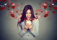 Jeune femme recevant le message textuel de sms d'amour au téléphone portable Photo libre de droits
