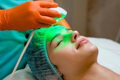 Jeune femme recevant le traitement de laser d'Epilation sur le visage au centre de beauté photo stock