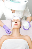 Jeune femme recevant le traitement facial Images stock