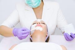Jeune femme recevant le traitement facial Image stock