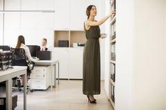 Jeune femme recherchant quelque chose dans le bureau Photos stock