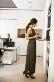 Jeune femme recherchant quelque chose dans le bureau Photographie stock libre de droits