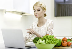 Jeune femme recherchant une recette sur l'ordinateur portable dans la cuisine photo stock