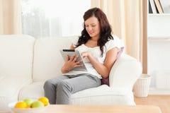 Jeune femme red-haired retenant une tablette Image libre de droits