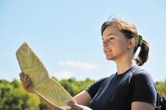Jeune femme regardant dans la carte Photo libre de droits