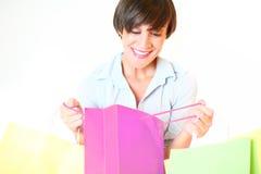Jeune femme regardant dans le sac à provisions Photographie stock libre de droits