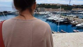 Jeune femme regardant des yachts dans le port maritime méditerranéen, rêvant de la vie riche banque de vidéos