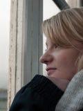 Jeune femme regardant hors d'une fenêtre photographie stock