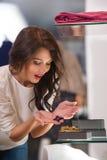 Jeune femme regardant l'étalage de boutique Photographie stock