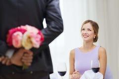 Jeune femme regardant l'homme avec le bouquet de fleur Photos stock