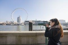 Jeune femme regardant l'oeil de Londres par la visionneuse stationnaire à Londres, Angleterre, R-U Image libre de droits