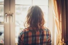 Jeune femme regardant la fenêtre photo libre de droits