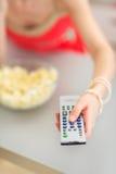 Jeune femme regardant la TV et mangeant du maïs éclaté Photo libre de droits