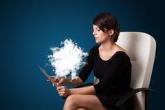 Jeune femme regardant le comprimé moderne avec le nuage abstrait Photographie stock libre de droits