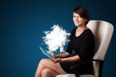 Jeune femme regardant le comprimé moderne avec le nuage abstrait Photo stock