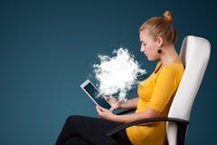 Jeune femme regardant le comprimé moderne avec le nuage abstrait Photos libres de droits