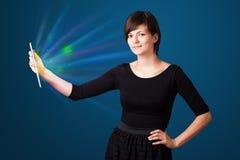 Jeune femme regardant le comprimé moderne avec les lumières abstraites Photographie stock libre de droits