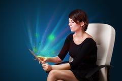 Jeune femme regardant le comprimé moderne avec les lumières abstraites Photo libre de droits