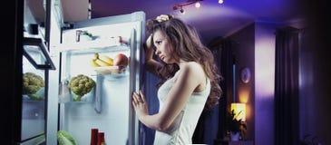 Jeune femme regardant le réfrigérateur Photo stock