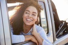 Jeune femme regardant loin hors de la fenêtre ouverte d'une voiture image libre de droits