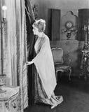Jeune femme regardant par derrière ses rideaux (toutes les personnes représentées ne sont pas plus long vivantes et aucun domaine Image stock