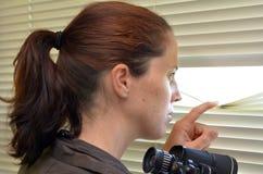 Jeune femme regardant par des abat-jour Photos stock