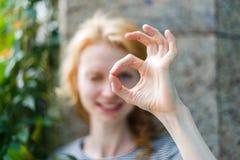 Jeune femme regardant par des doigts montrant le signe CORRECT Photographie stock libre de droits