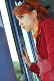 Jeune femme regardant par l'hublot de monorail Images stock