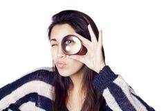 Jeune femme regardant par la loupe Image stock