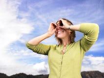 Jeune femme regardant par les mains évasées Photo stock