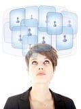 Jeune femme regardant ses amis virtuels d'isolement Image libre de droits