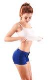 Jeune femme regardant son corps mince d'isolement sur le blanc photos stock