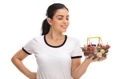 Jeune femme regardant un petit panier à provisions Photos stock