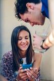 Jeune femme regardant un smartphone avec son ami dehors Photographie stock