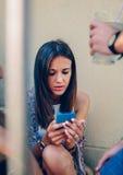 Jeune femme regardant un smartphone dehors avec elle Photographie stock