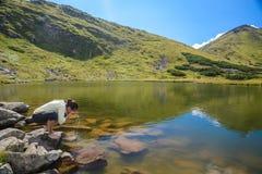 Jeune femme reisting à un lac photographie stock