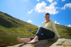 Jeune femme reisting à un lac images stock
