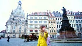 Jeune femme renversante montrant l'amie dans le voisinage visuel d'appel de la ville européenne l'après-midi frais dehors Dresde banque de vidéos