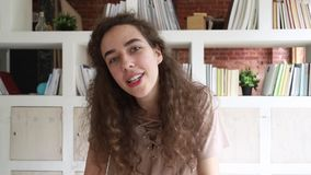 Jeune femme reposant à l'intérieur des entretiens par l'intermédiaire du webcam regardant la caméra clips vidéos