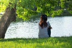 Jeune femme reposant sur la berge sous l'arbre sur la tête son usage il image stock