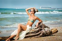 Jeune femme reposant sur la procédure de connexion la plage Image libre de droits