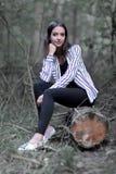 Jeune femme reposant sur un identifiez-vous les bois photographie stock libre de droits