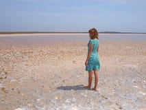 Jeune femme restant sur un lac de sel photo stock