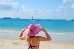 Jeune femme restant sur une plage Photographie stock libre de droits