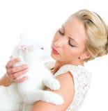 Jeune femme retenant le chat blanc. Image libre de droits