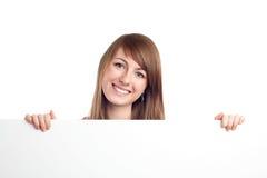 Jeune femme retenant le panneau-réclame blanc Image stock
