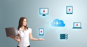Jeune femme retenant un ordinateur portable et présent le netw de calcul de nuage Image libre de droits